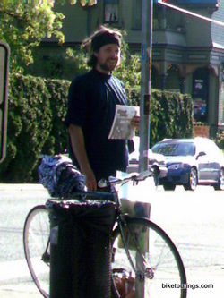 Picture of homeless person selling newspapers with a bike