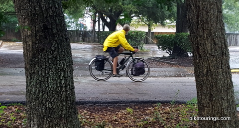 Picture of bike commuter riding touring bike with waterproof rain gear