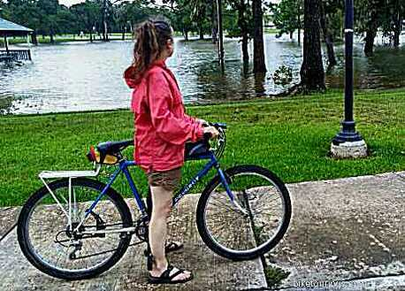 Picture of woman riding her touring bike with rain jacket