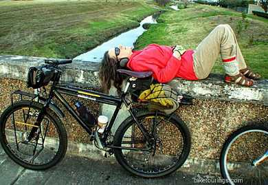 Picture of woman laying down next to bike for bikepacking