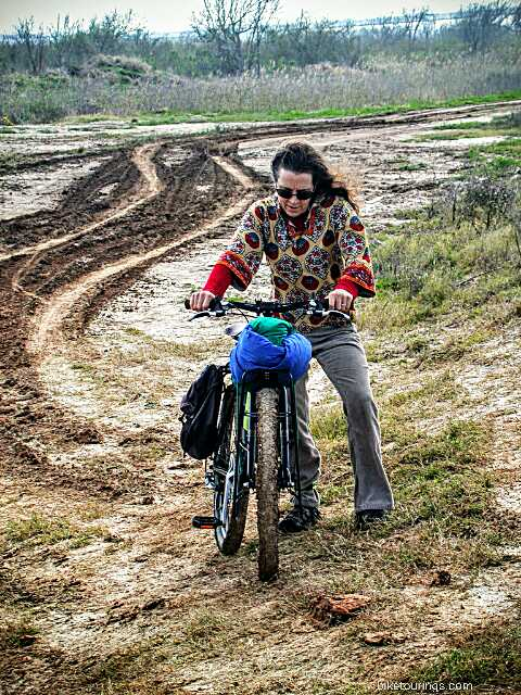 Picture of woman pushing loaded touring bike through muddy road.