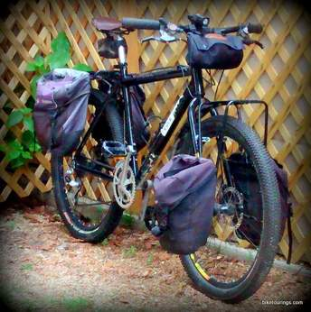 Picture of axiom front and rear panniers with with handlebar bag for bikepacking and bicycle touring