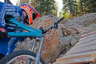 Picture of mountain bike rider carrying bike on Psycho Rocks trail at Crested Butte Resort, CO