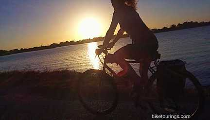 Picture of woman riding a touring bike at sunrise